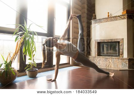 Young attractive woman practicing yoga, stretching in Side Plank exercise, Full Version of Vasisthasana pose, working out, wearing sportswear, pants, indoor full length, home interior, living room