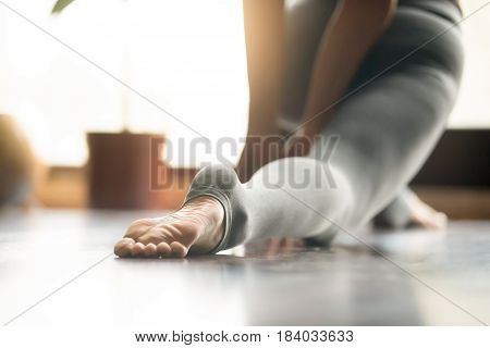 Young woman practicing yoga, stretching in anjaneyasana exercise, Horse rider pose, working out, wearing sportswear, grey pants, indoor, home interior, living room close up, foot in the focus