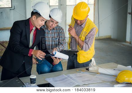 Management Consulting And Engineers And Foreman Working With Blueprint And Drawing On Work Table For