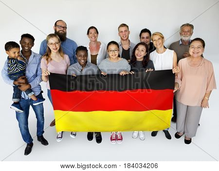 People in group holding country flag and posing for photoshoot