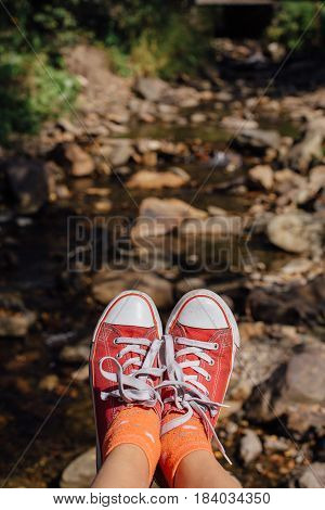 Red canvas sneakers shoes on the feet. Top view