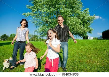 a family and their pet dog are running on a green meadow in a park
