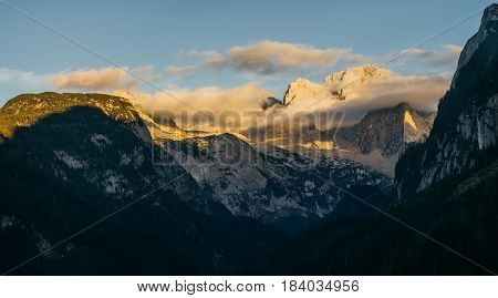 Panorama of Dachstein mountains in sunset light Austria. Peaks covered with clouds