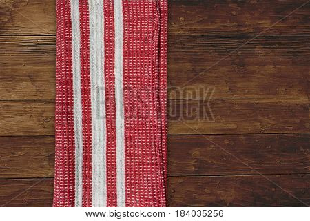 Red napkin with white stripes over wooden table top view background