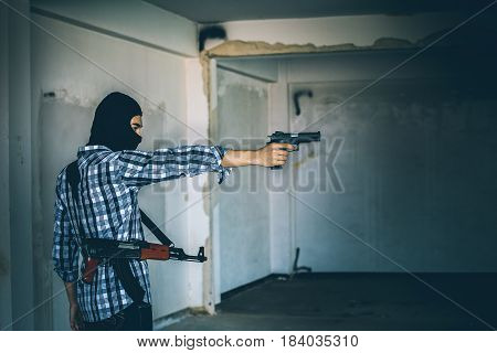 Robber Holding A Gun At Abandoned Building. Low Key Photo And Selective Focus. Criminality Concept.