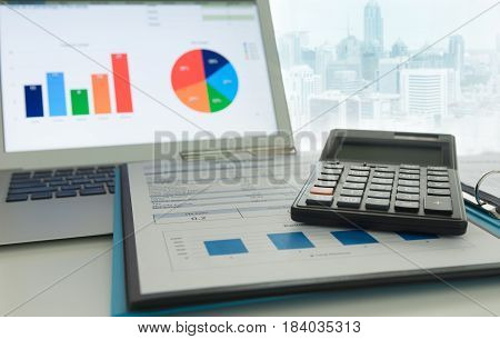 Financial adviser are calculation and the report analyzes the business and computer showing graph and chart.