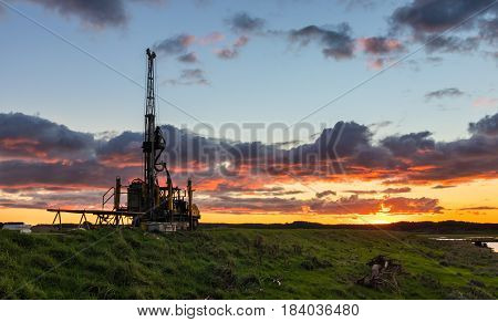 Portable drill rig on a stop bank at sunset.