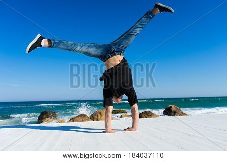 Young Athlete doing handstand on the beach. Street workout. break dancer man standing on two hands