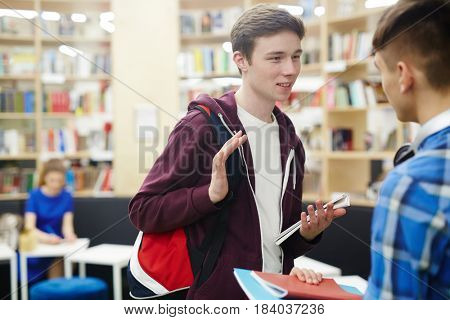 Two guys discussing book or home assignment in library