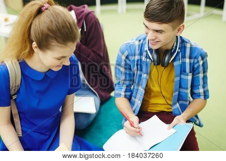 Teenage students discussing homework after lesson
