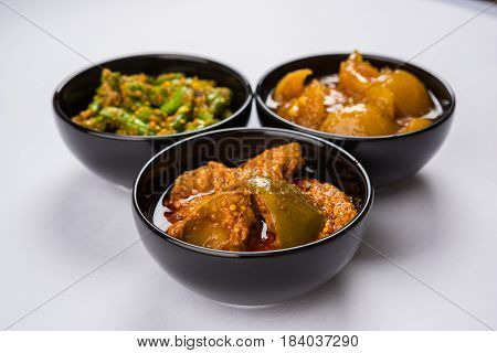 Group photograph of indian pickles like mango pickle , lemon pickle and green chilli pickle, sarved in ceramic bowls, selective focus