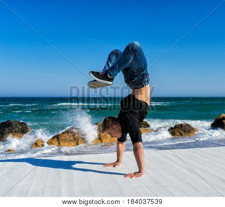 Young Athlete walkimg on hands on the beach. Street workout. break dancer man doing handstand