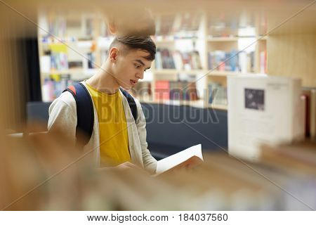 Curious guy reading book in college library