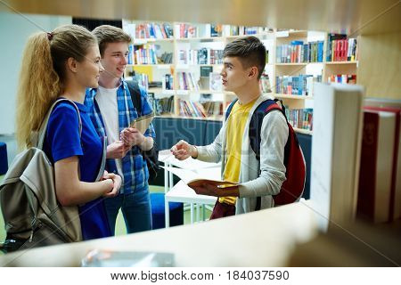 Adolescent student explaining home assignment to groupmates