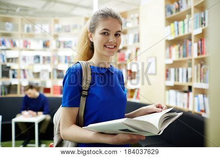 Pretty learner with opeen book looking at camera