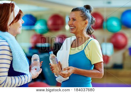 Aged buddies having drink after workout in gym