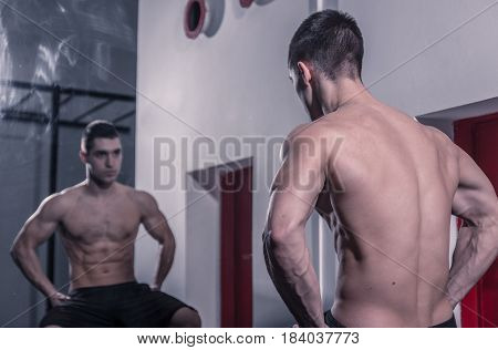 One Young Man Bodybuilder Looking At Himself In Mirror