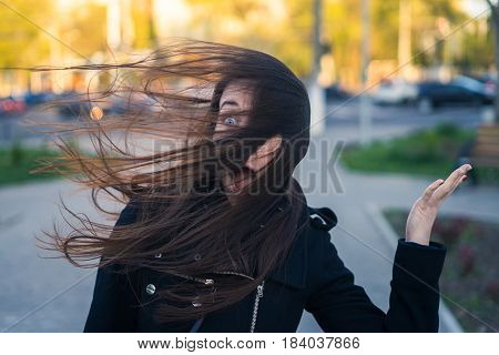 emotions of beautiful young girl in the city - she is shocked and screaming. Strong wind blows her hair