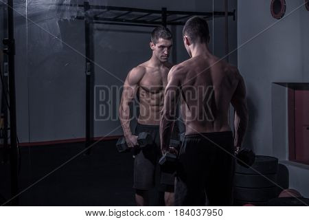 One Young Man Bodybuilder, Looking At Himself, Holding Dumbbells