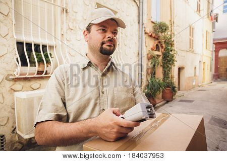 Messenger delivering parcel, standing in the street of a french town