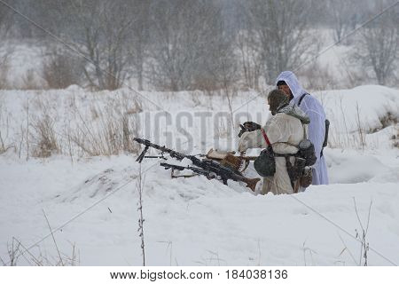 LENINGRAD REGION, RUSSIA - JANUARY 15, 2017: German machine-gunners of the Second World War take a position. Fragment of the military-historical reconstruction of the battles for the lifting of the blockade of Leningrad