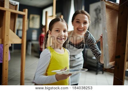 Young school teacher and learner with watercolors standing by easel in art studio