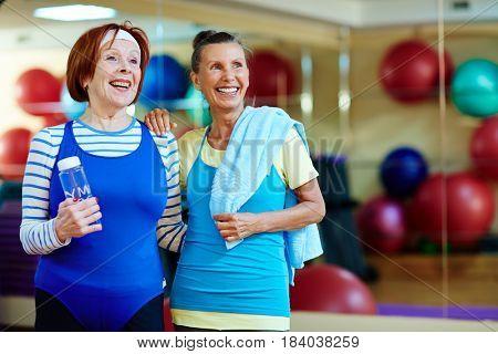 Cheerful grandmas in activewear looking at something curious in gym
