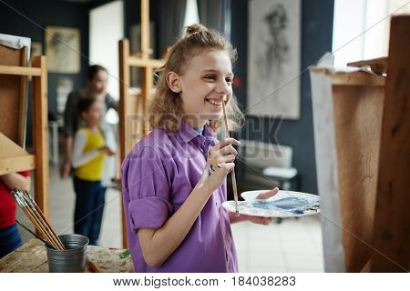 Happy schoolboy with watercolors and paintbrush looking at his painting