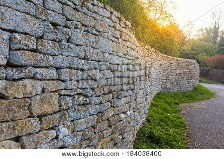 old traditional Cotswolds stone fence wall shown in leading perspective with sun flare