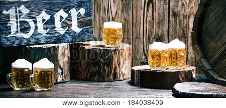 Mugs of beer on raw wood pub counter with natural stumps and fragment of oak barrel. Wood signboard with text 'Beer'