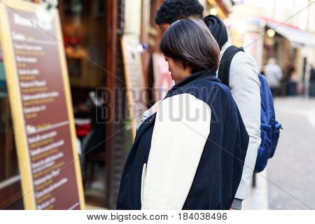 Multi-ethnic couple having fun in Paris, Latin Quarter, near Notre Dame Cathedral. Looking at a restaurant's menu.