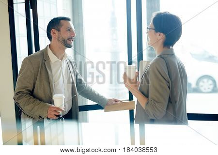 Friendly co-workers with hot drinks leaving cafe