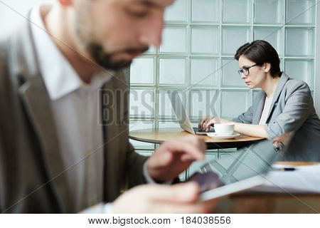 Serious businesswoman typing and browsing in the net in working environment