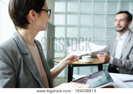 Young economist giving financial documents to colleague