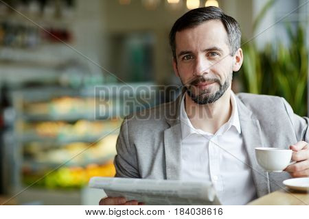 Happy businessman with paper and cup of coffee having break in cafe