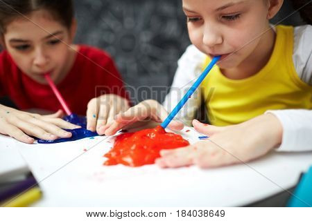 Two kids taking in slimes through plastic straws