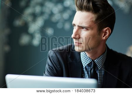 Serious young man concentrating on thoughts