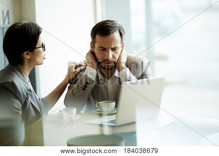 Tense businessman looking at laptop display while colleague comforting him