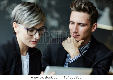 Attentive businessman listening to explanation of co-worker