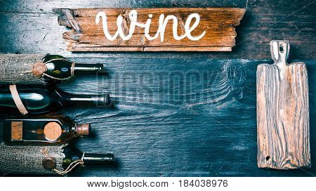 Vertical line of various vintage sealed wine and brandy bottles. Rustic wood cutting board on the side and signboard above. Black textured wood background. Old-fashioned style. Top view