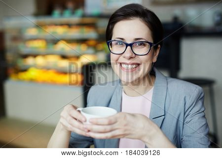 Happy businesswoman with cup of drink sitting in cafe