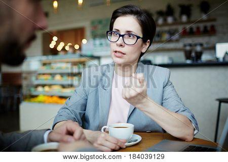 Serious economist explaining her colleague something important