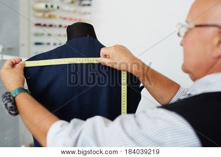 Closeup portrait of grey haired old man measuring back on mannequin in traditional tailoring studio