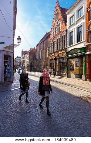 Bruges Belgium - 11 April 2017 - Tourists and local Belgians walk around street of world heritage city Bruges Belgium on April 11 2017.