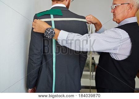 Old fashioned tailor taking back measurements from client in small atelier studio to make custom classic suit with jacket