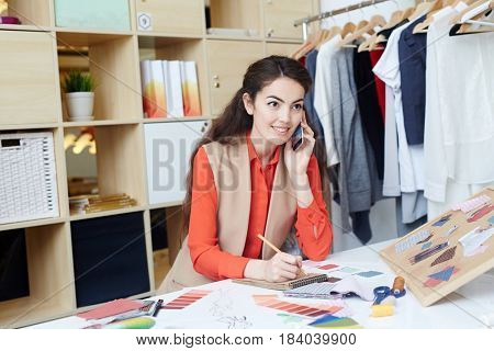 Dressmaker assistant with cellphone taking order from one of clients