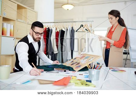 Serious couturier drawing fashion sketches while his assistant working with clothes
