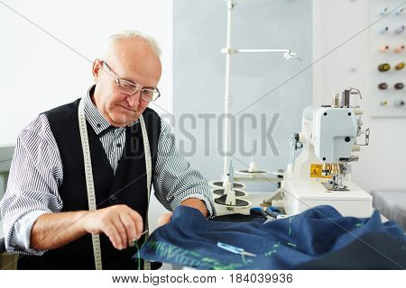 Portrait of old man working in tailoring studio making clothes at sewing machine and hand stitching cloth