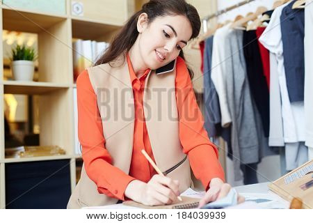 Contemporary fashion designer speaking with client by cellphone