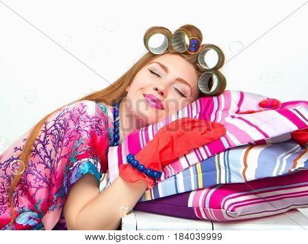 woman a housewife or a small business owner and entrepreneur at robe curlers on her heel doing laundry and cleaning the house sat down to rest on the pillows sexy housewife cleaning concept Portrait
